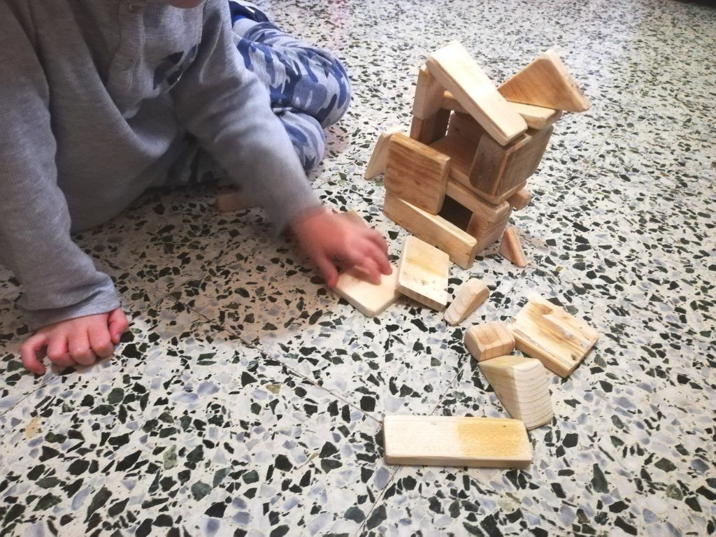 Boy playing with wooden game on the floor